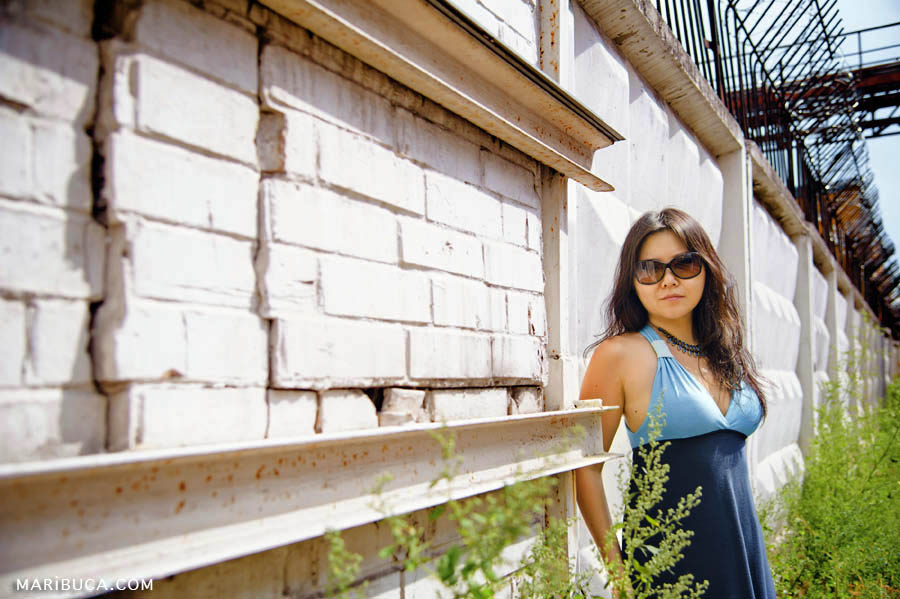The girl in the blue dress and sunglasses standing against a white fence.