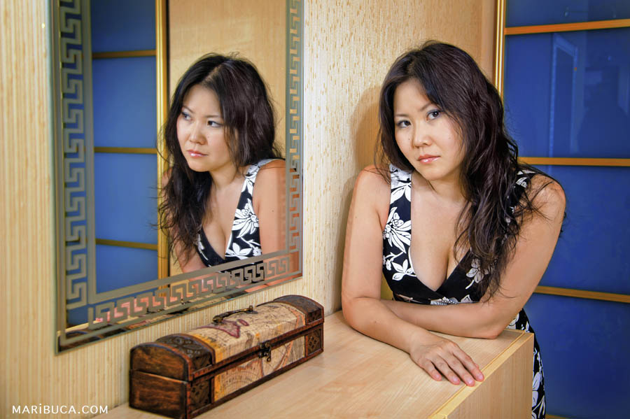 Portrait of a girl with long with her reflection in a mirror in beige and blue tones