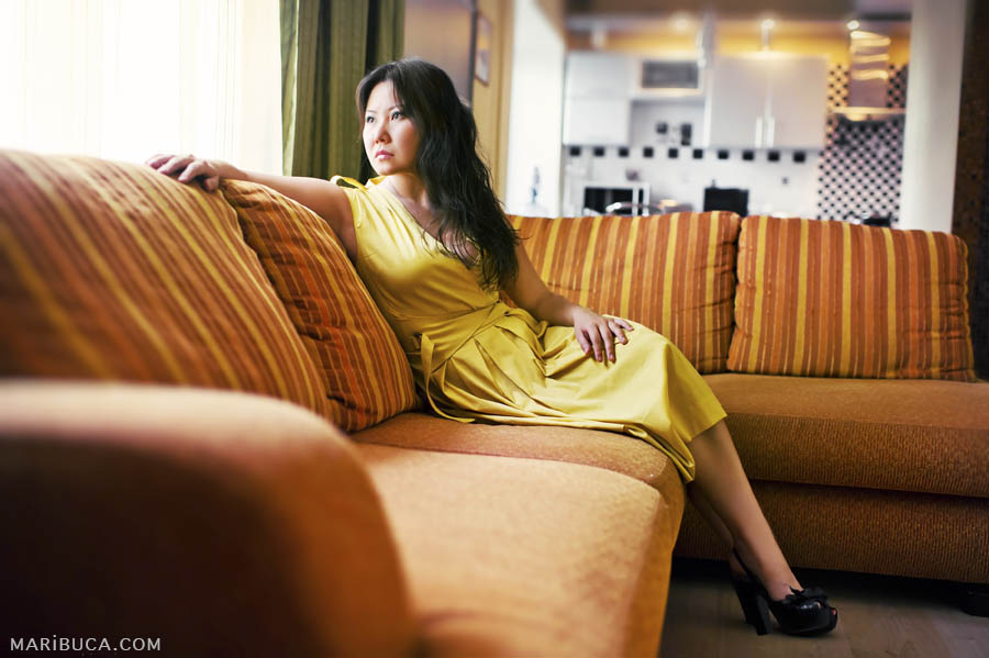 Portrait of a girl in a yellow dress on the background of an orange sofa looking out the window