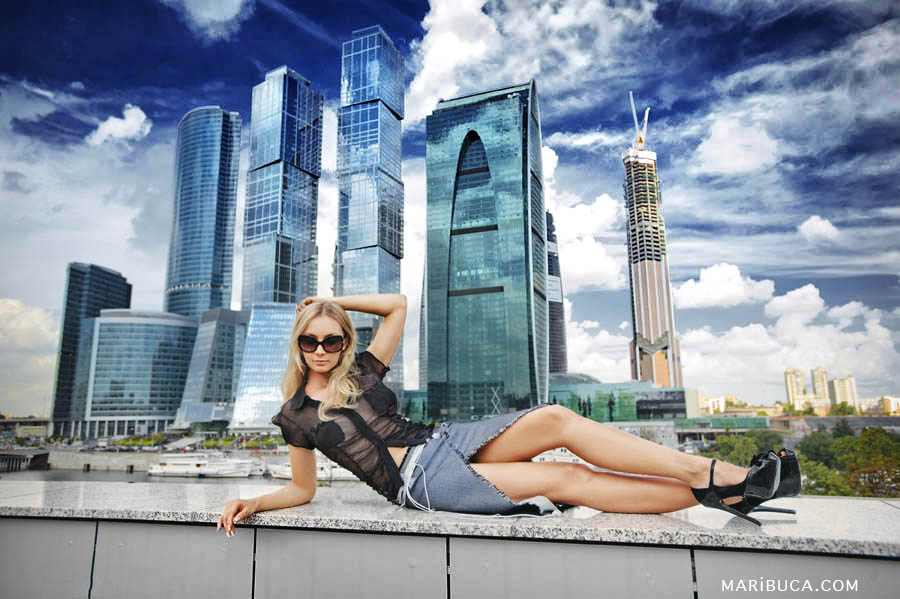 elegant girl model in a black translucent sweater and short denim skirt lies against the background of downtown in San Francisco
