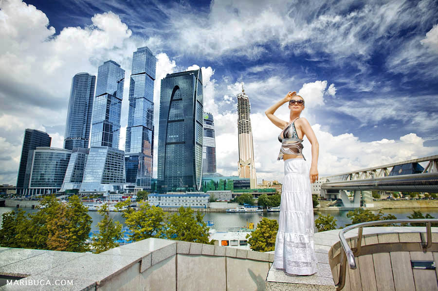 A tall girl in a white long skirt stands in front of tall buildings in downtown San Francisco.