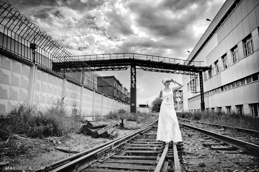A black and white photo of an Industrial view of a factory with old rails and a girl standing in a white T-shirt and white long skirt at Campbell.