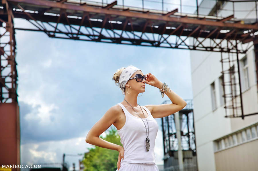 Portrait of a girl in a white T-shirt, bandana and sunglasses in industrial style against a blue sunny sky