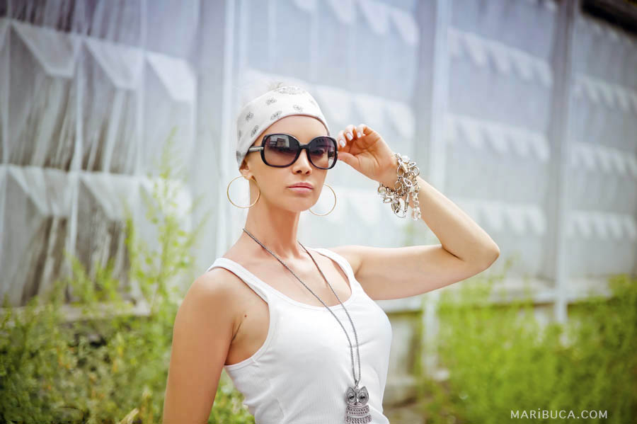Portrait of a girl in a white T-shirt, bandana and sunglasses in industrial style against a white fence