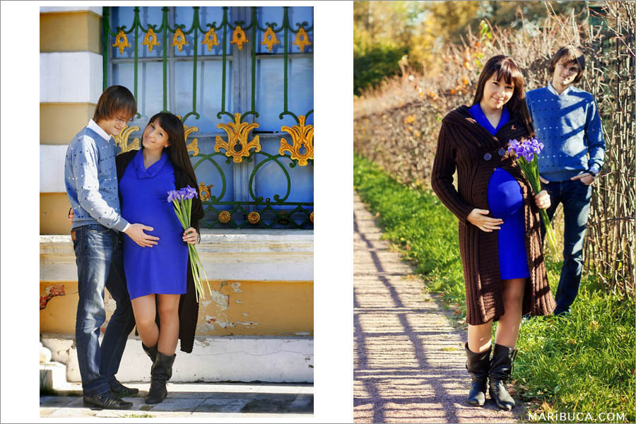 photo session of future parents. A pregnant girl in a Navy Blue dress and lilac flowers hugs her husband in San Francisco Park.