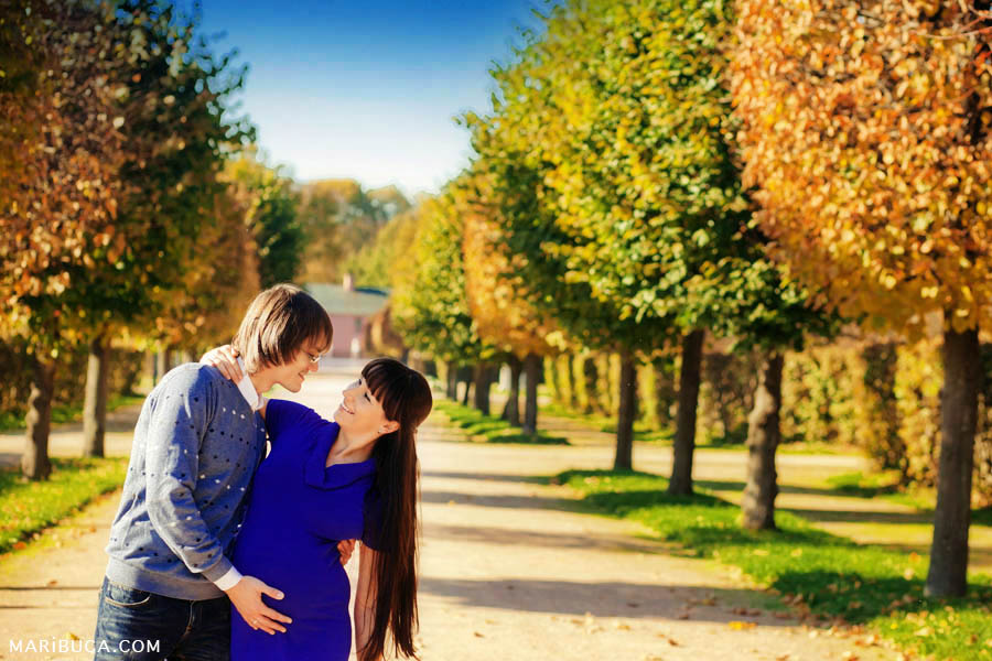 Pregnant photography where the girl embraces and looks at her husband touches wife's belly