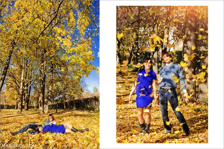 Maternity photoshoot in golden autumn. The boy and the girl are having fun throwing yellow leaves, laughing and waiting for the baby to wait.