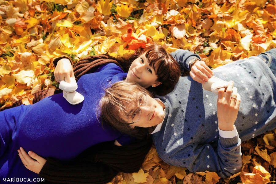 Pregnant girl and her husband lie on the yellow-orange leaves in San Francisco