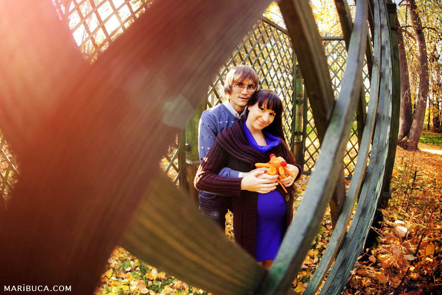 Future parents hug each other and standing inside a decorative green fence with red rays