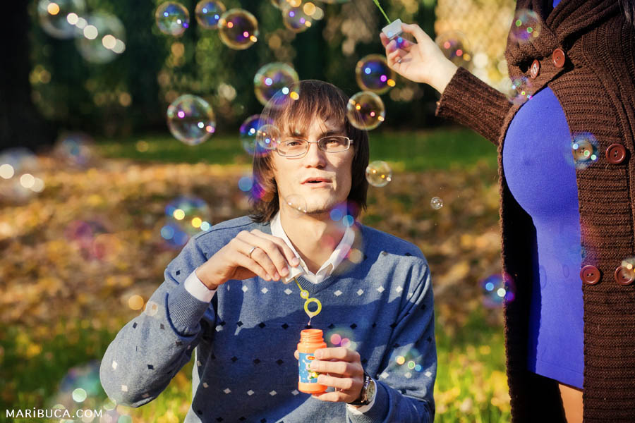 The guy in a light blue sweater launches colored soap bubbles and a pregnant wife standing to his left.