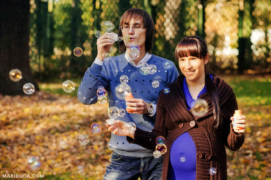 Newlyweds expect the first baby and have fun on the street in sunny autumn weather launching soap bubbles.