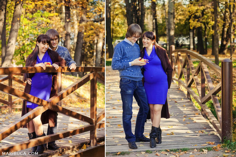 Couple, where wife is expecting the first child are standing, hugging and laughing in the wooden bridge.