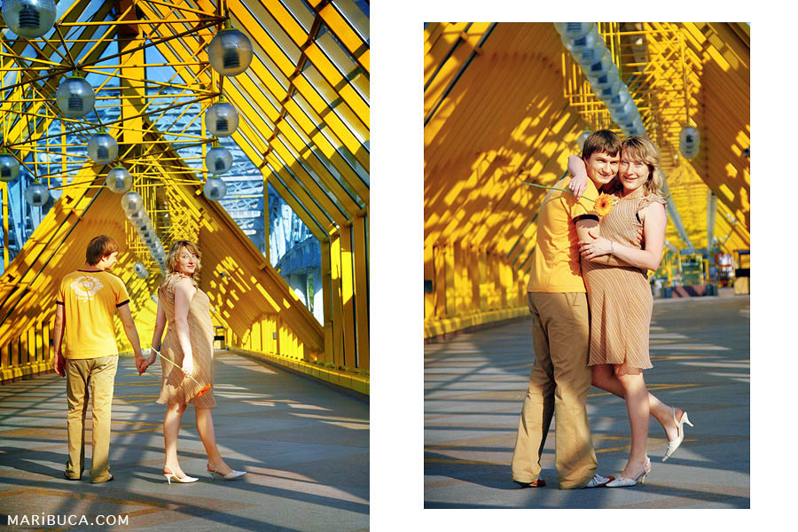 Pregnant couple stand on a bridge surrounded by yellow elements of the building