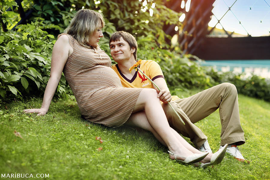 Pregnant girl and her husband are lying on the grass and looking at each other with love.