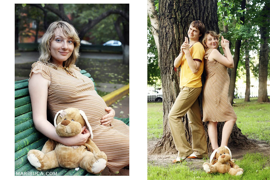 Portrait of a pregnant girl holding gently her belly and a soft toy. Couple stands back to each other and depict a gangster style against the tree in the park.
