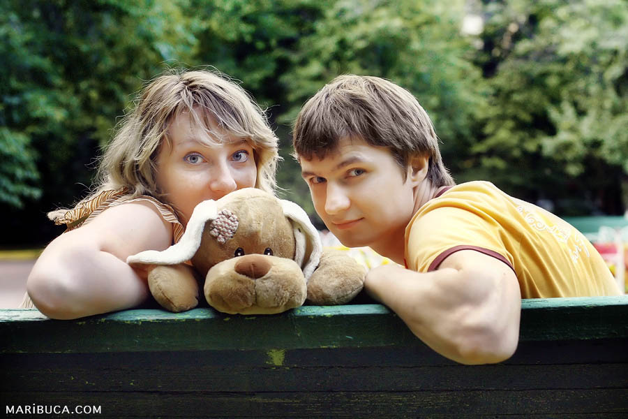 Portrait of a girl, a guy and a soft toy dog sitting on a bench against the background of green trees in the park.