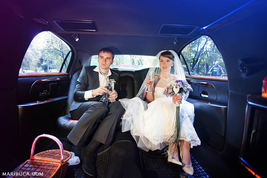 the bride and groom are sitting in a limousine and going to a photo session in front of the registry office
