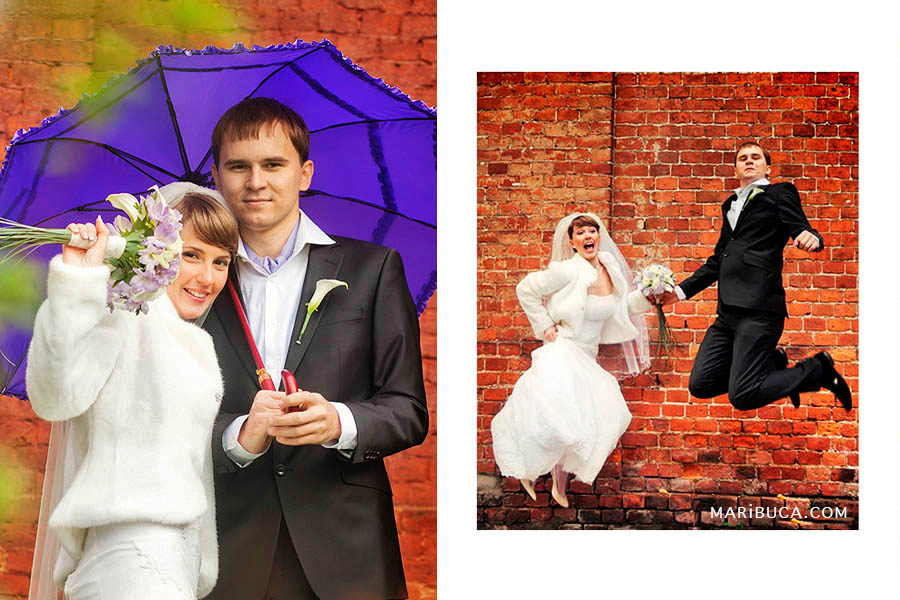 Bride and groom under a purple umbrella and jumping from happiness on the background of a red-brick wall
