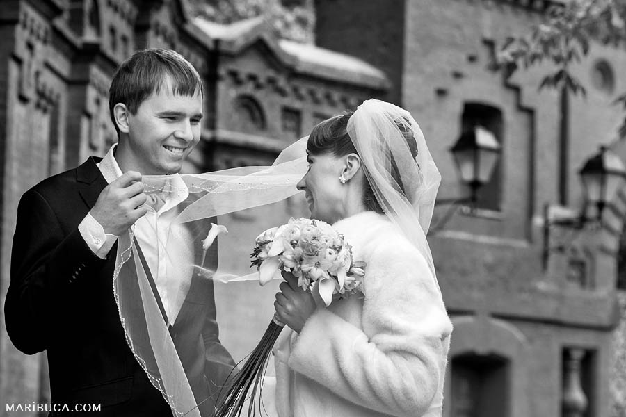 The groom looks tenderly at the bride and holds her veil against the background of the church.