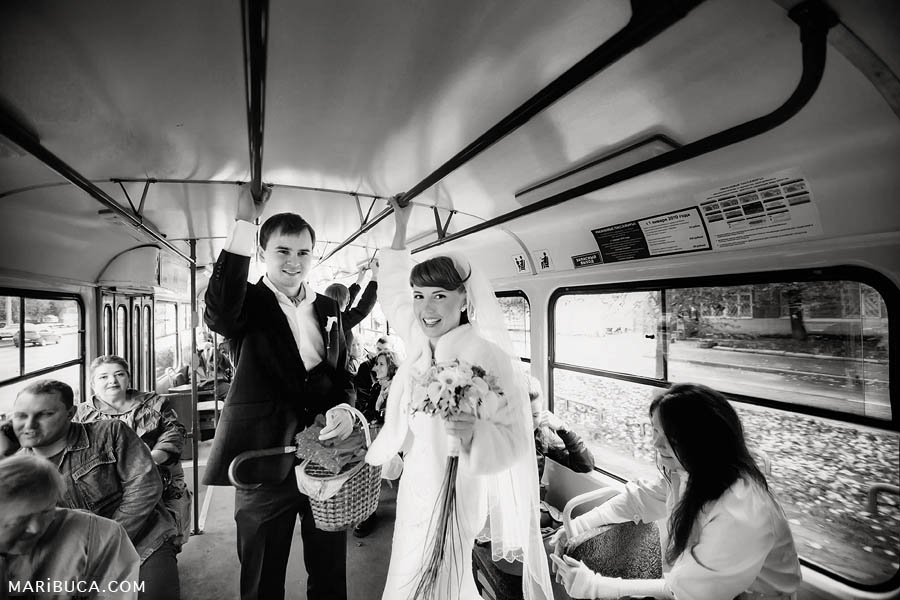 black and white photograph of the bride and groom standing in public transport in the tram and go to the registry office San Francisco City Hall.