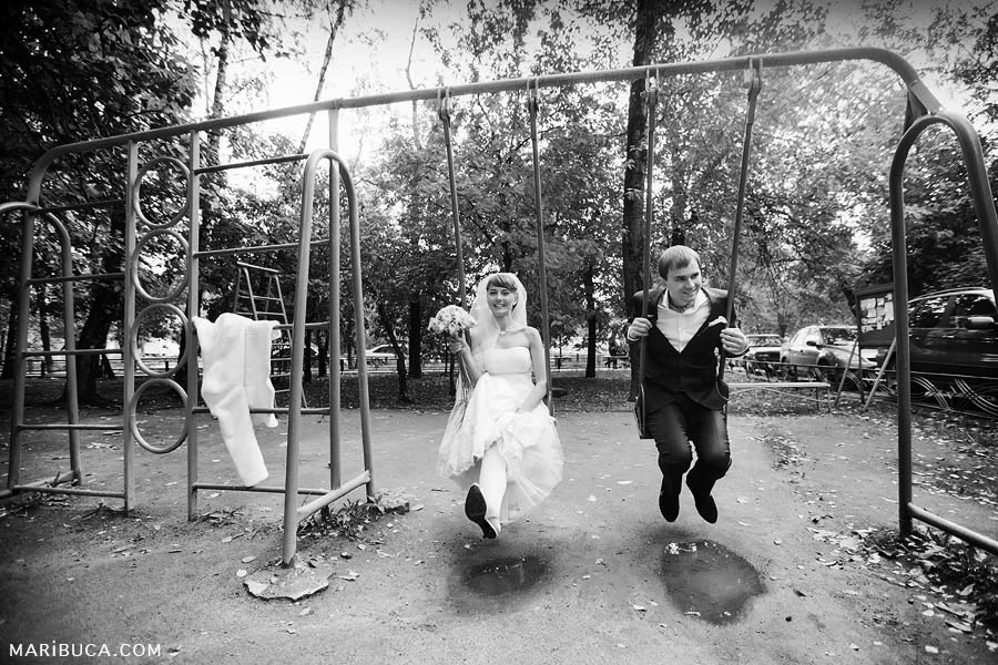 black and white photograph of the bride and groom on a swing on the playground, remember their childhood