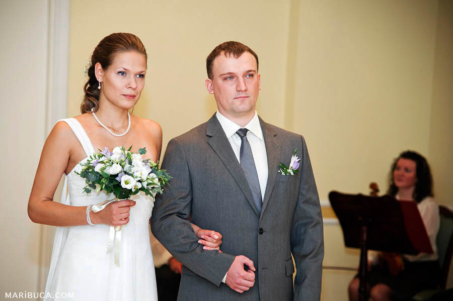 Groom and bride took serious look during wedding ceremony in the register office.
