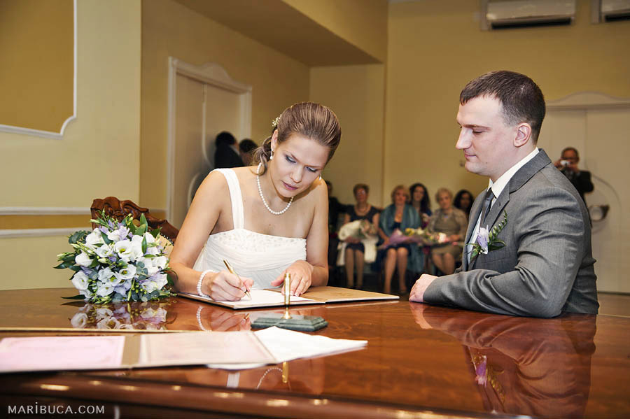 Bride and groom signs their marriage certificate in the register office.