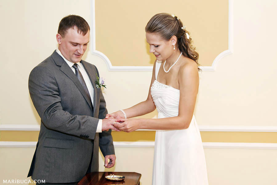 Groom put the wedding ring on the bride's finger in the wedding ceremony