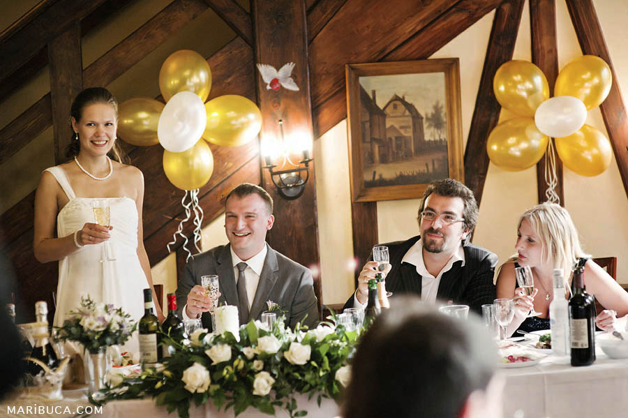 Guests make toasts for newlyweds couple in the barn around yellow and white balloons in the wall.