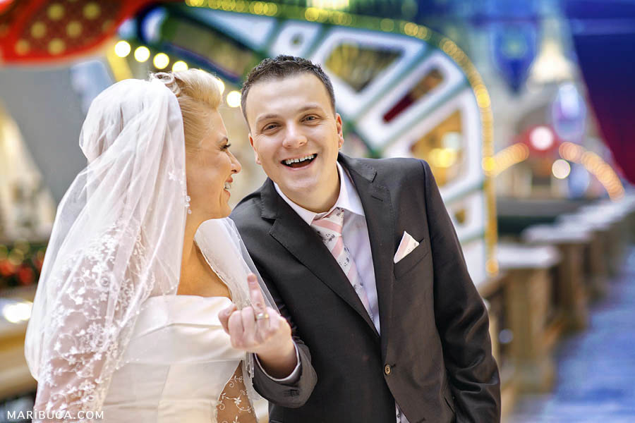 The groom shows wedding ring in his finger and laughing.