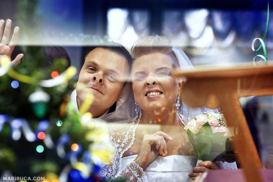 The groom and the bride make silly faces using the window in the shopping mall, San Jose.