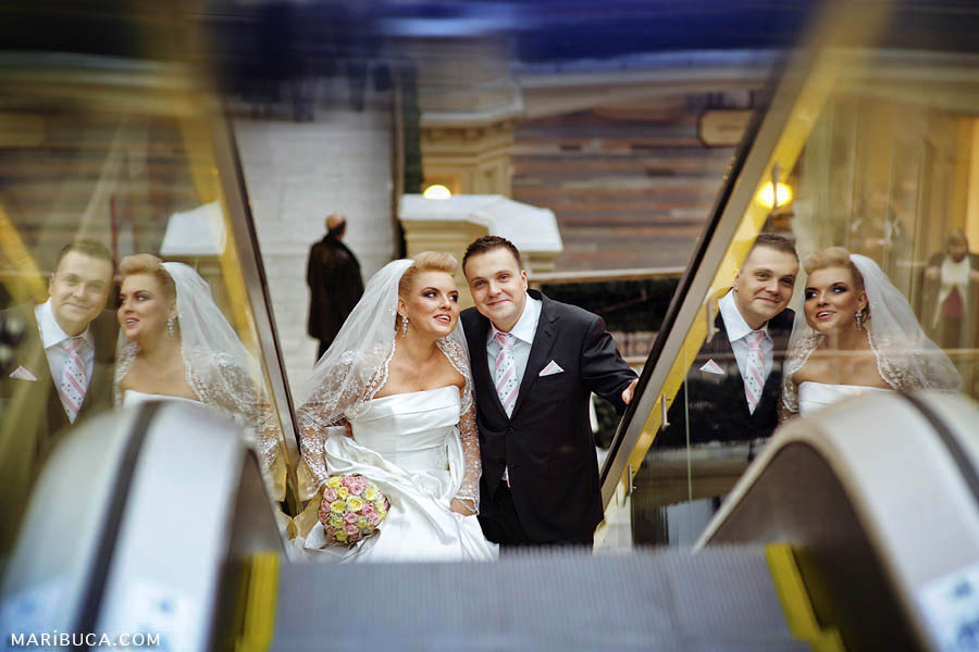 Triple images of the bride and groom in reflections from the glass of the escalator in the Fairfield, San Jose.