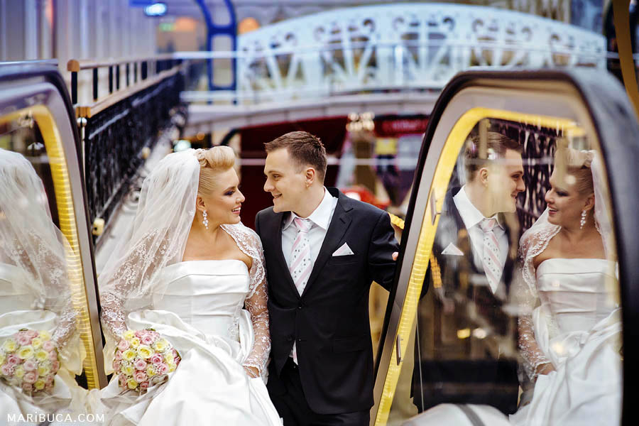 Portrait of newlyweds and reflection from the escalator in the shopping mall.