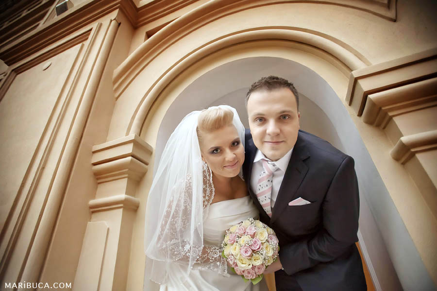 Newlyweds look in the camera and hold light pink and white wedding bouquet.