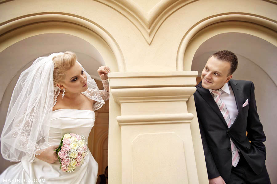 the bride and groom stand from different sides and each in their own arch and look at each other