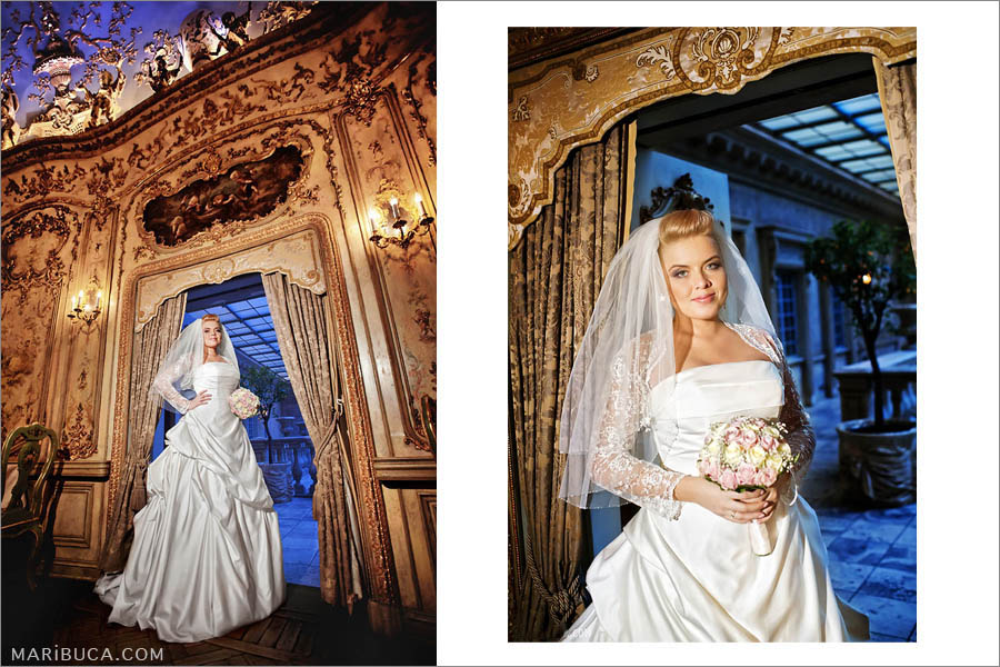 bride stands in the arch on the background of the yellow wall with candelabra