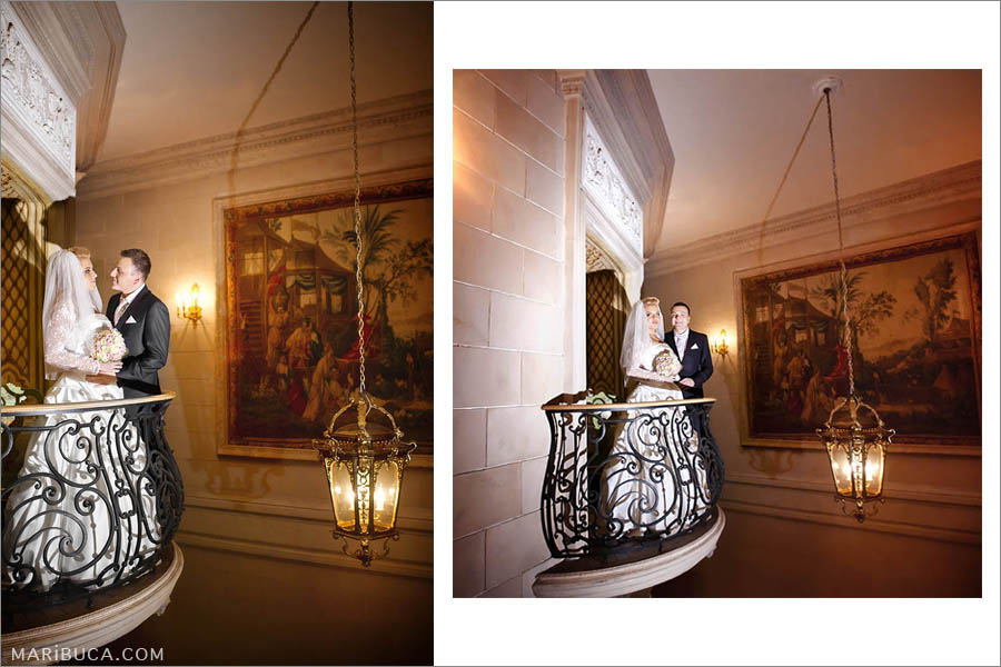 the bride and groom stand on a decorative balcony against the background of hanging chandeliers and paintings.