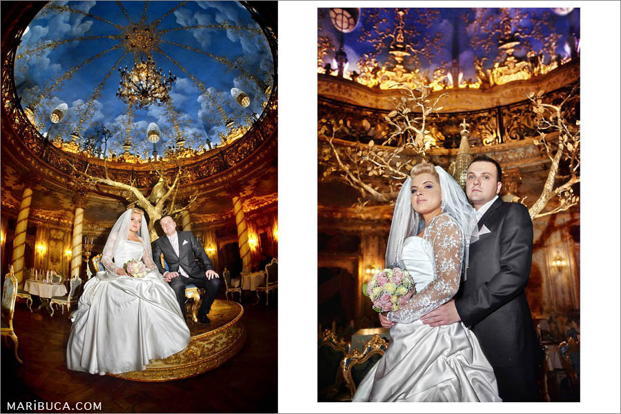 the bride and the groom are sitting in the golden hall against the blue painting of the blue sky.