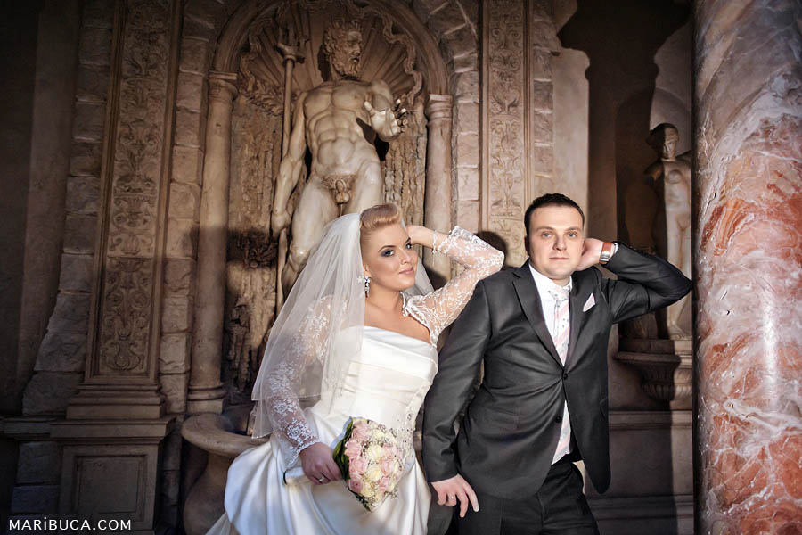 the bride leaned on the groom's shoulder against the background of the statue of Neptune
