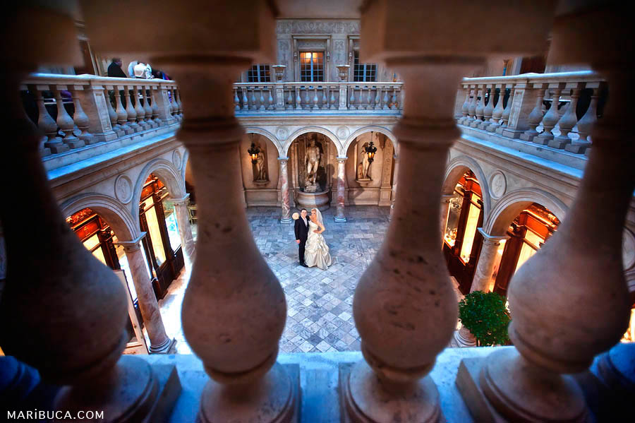 A magnificent hall with columns in the blue light and in the middle of the hall stand the bride and groom and look at each other.