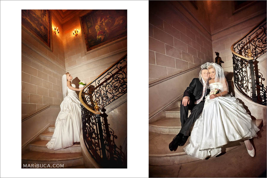 Bride and groom are sitting in the staircases against beige and brown backdrop.