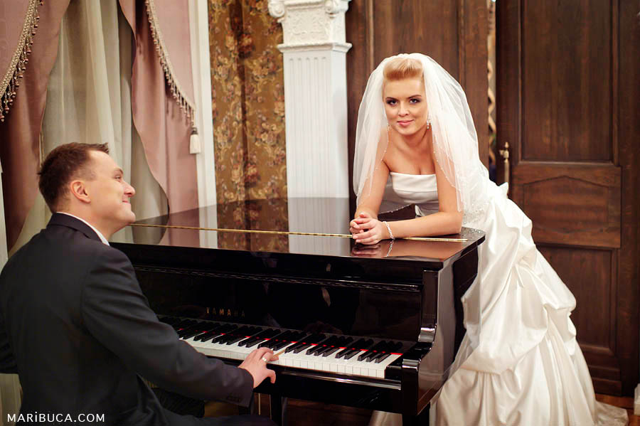 the bridegroom plays at the black piano, while the bride leans it and listens to him.