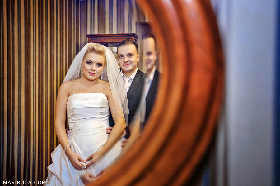 the bride and groom look through the mirror on the background of brown-beige wallpaper and rounded brick-colored mirror.