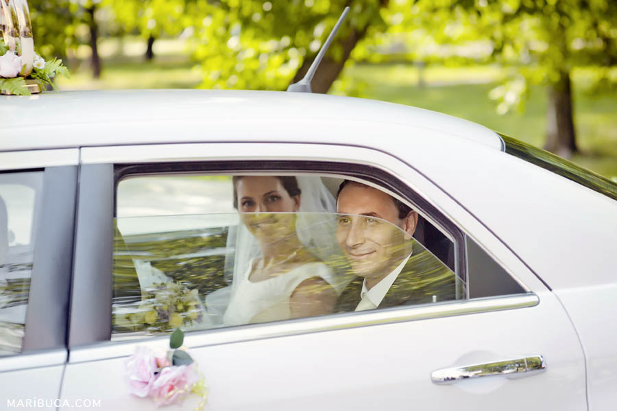 the bride and groom are sitting in a white car with the window ajar and smiling