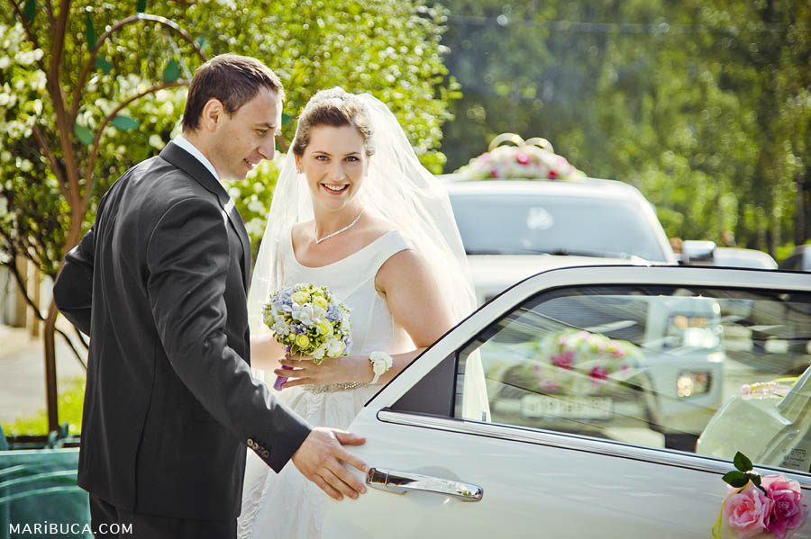 the groom opened the car door for the bride, the happy bride stands next to the groom in front of the registry office.