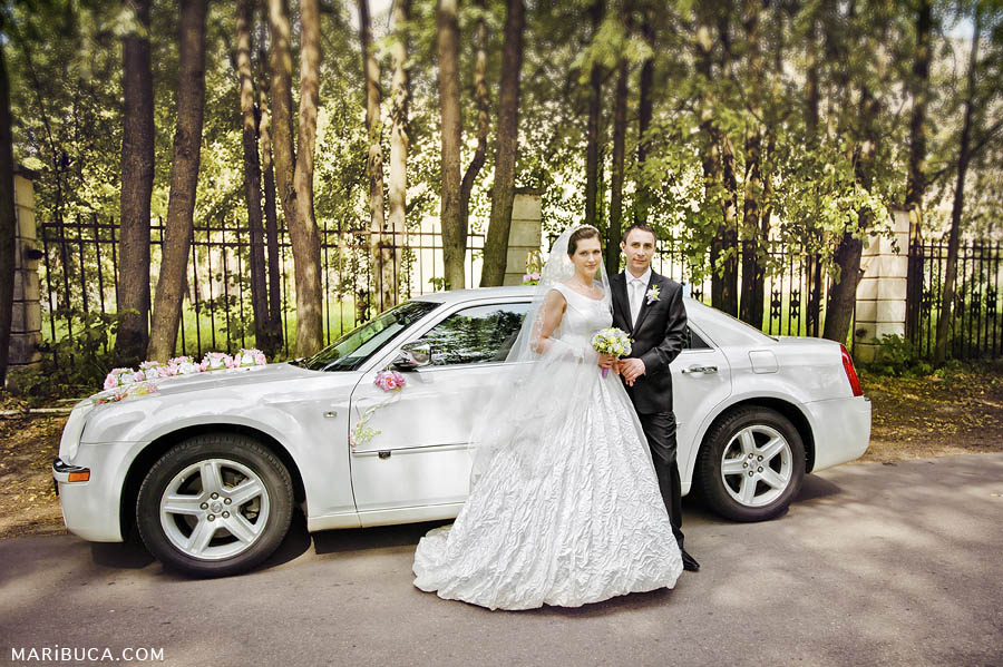 bride and groom stand in front of a white car Bentley on the background of trees