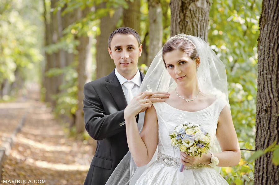 the bride and groom touching each other and posing against a background of trees receding into the distance