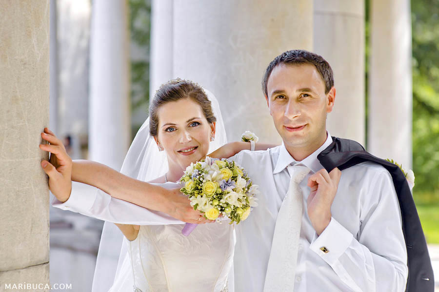 the groom holds a jacket over his shoulder, the bride leaned on the groom's hand and holds a light yellow bouquet against the white columns.