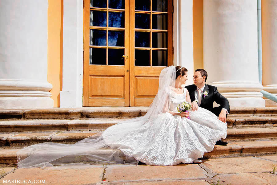 the bride and groom are sitting on the stairs of a building with huge white columns in sunny weather.