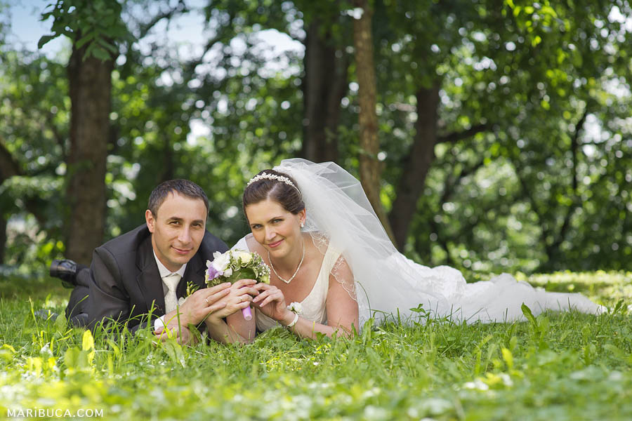 the bride and groom are lying on the grass and holding hands against the backdrop of a wonderful park in Fremont.